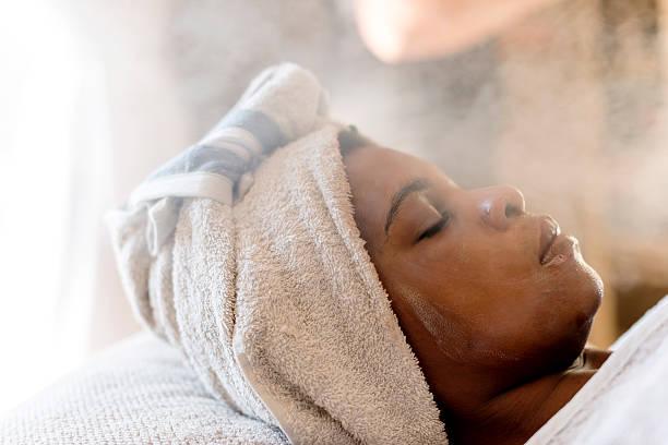Adult African Woman Relaxing & Enjoying A Facial Treatment At A Beauty Salon.